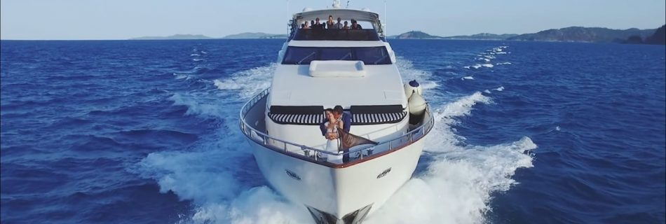 bride and groom on the front of 100ft luxury yacht drone