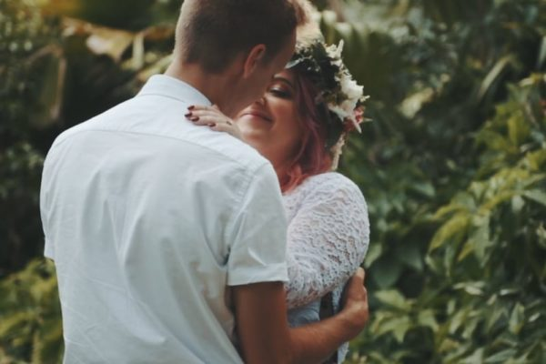 bride and groom embracing in rainforest