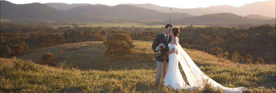 bride and groom standing in field embracing