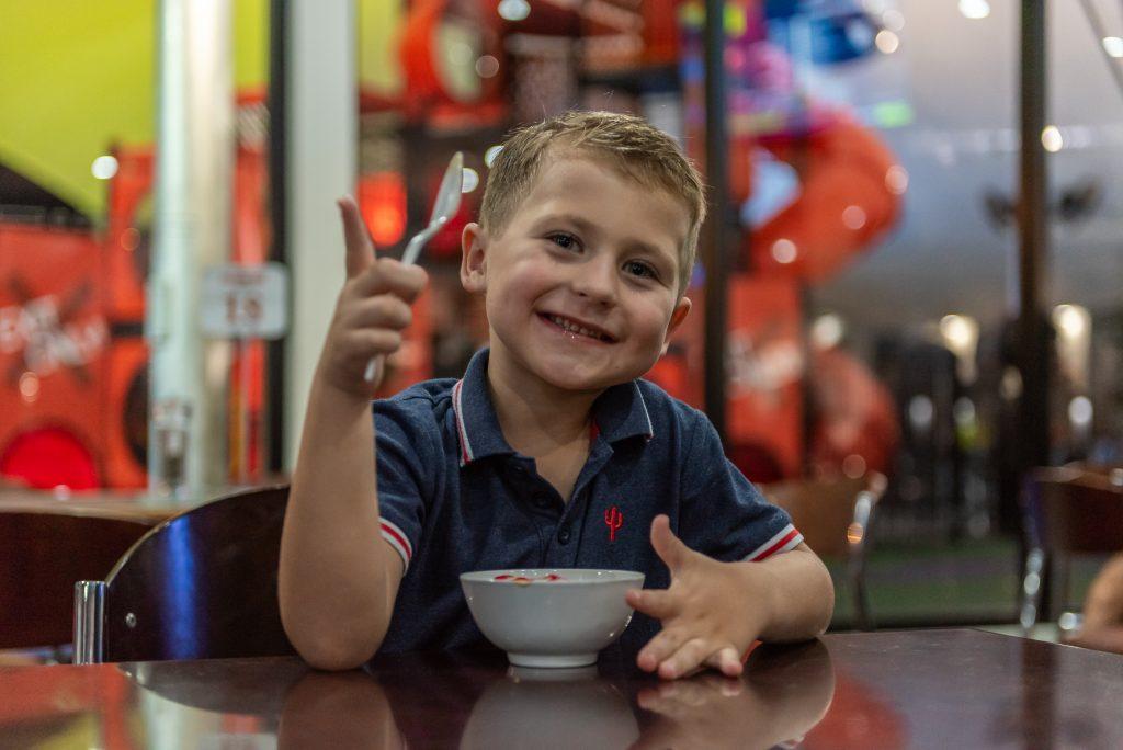 boy eating icecream with thumb up