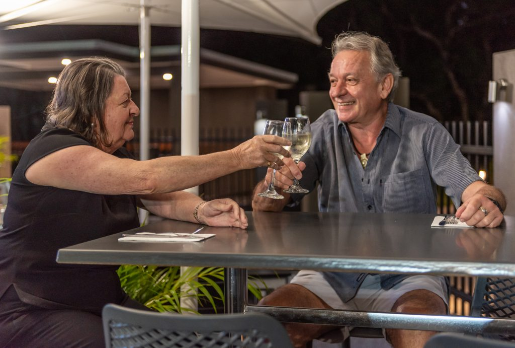 couple cheers glasses of wine