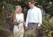 bride and groom holding hands foliage