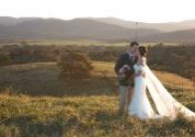 bride and groom standing in field embracing