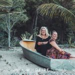 two women sitting in a boat on a beach